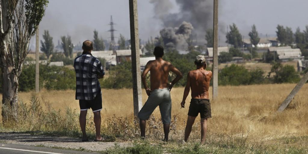 Un résident regarde de la fumée s'élever lors de bombardements, dans la ville de Novoazovsk, est de l'Ukraine, le mercredi 27 août 2014. Les rebelles séparatistes ont bombardé une ville dans le sud-est de l'Ukraine mercredi, faisant craindre qu'ils ne lancent une contre-offensive sur les zones de la région contrôlées par le gouvernement, le lendemain de la rencontre entre les dirigeants de l'Ukraine et de la Russie réunis pour discuter de l'escalade de la crise.(AP Photo/Sergei Grits) | ASSOCIATED PRESS